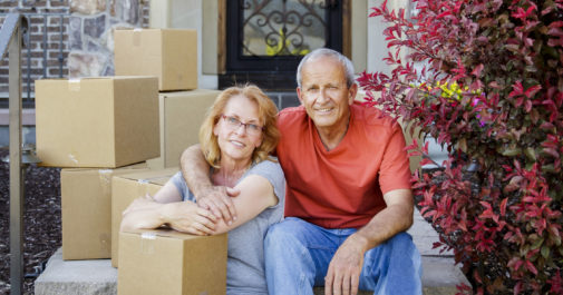 Mature couple sitting on steps in the front of their home with moving boxes.